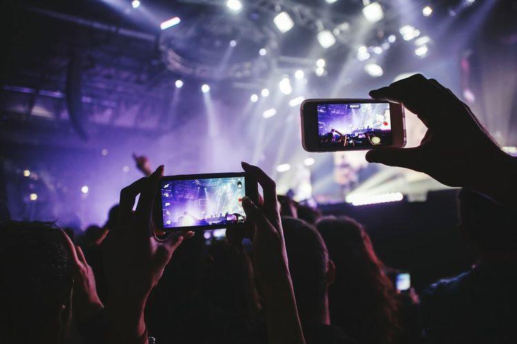 Fans holding smart phones at musical concert