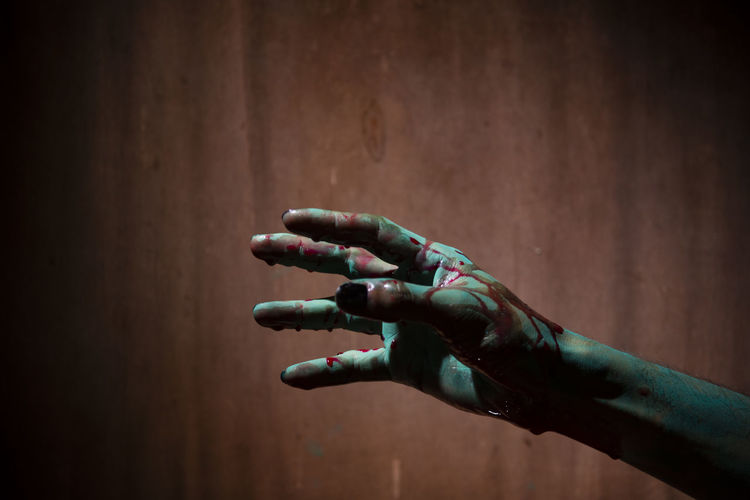 Painted spooky hand of woman in dark during halloween