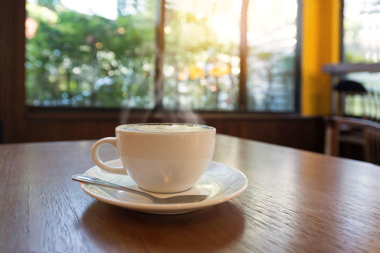 Cup of coffee on table in cafe morning light , vintage retro color effect Coffee Shop Coffee Time Morning Cafe Close-up Coffee - Drink Coffee Cup Cup Of Coffee Day Drink Food And Drink Freshness Hot Coffee Indoors  No People Refreshment Saucer Table Window Wood - Material