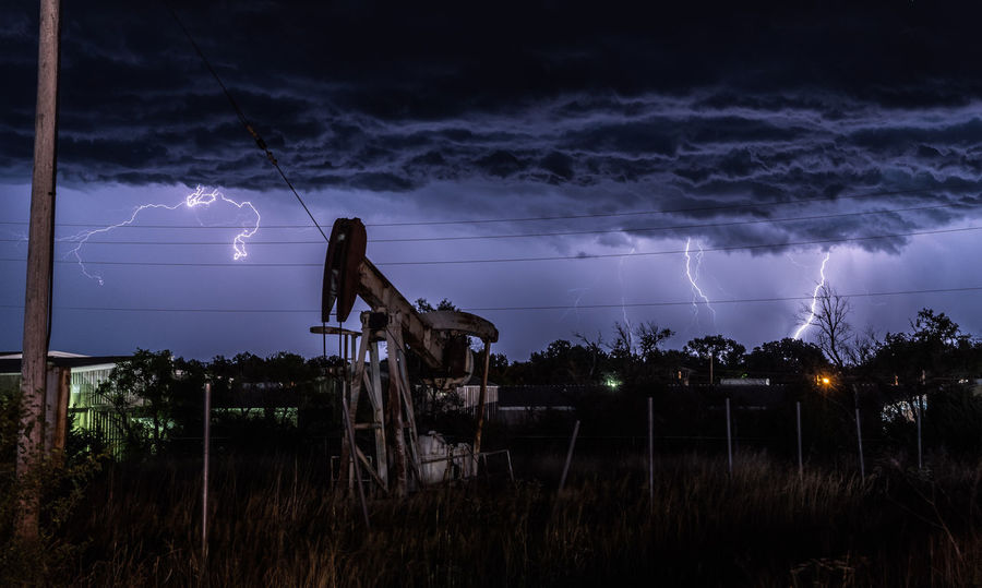 Lightning crackles over the outskirts of a Kansas town. An oil well pump jack is illuminated by the storm. Cloud - Sky Great Plains Kansas Lightning Night Pump Jack Sky Storm Storm Cloud Thunderstorm Weather The Great Outdoors - 2017 EyeEm Awards