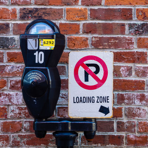 On-street parking meter Communication Sign Brick Brick Wall Wall - Building Feature Close-up Text Warning Sign Red Information Outdoors Architecture Wall Brick Wall Parking Meter Symbol Metal Parking Meter Parking Sign Coin Paysage Color Red Loading