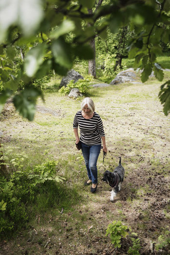 Full length of woman with dog against plants