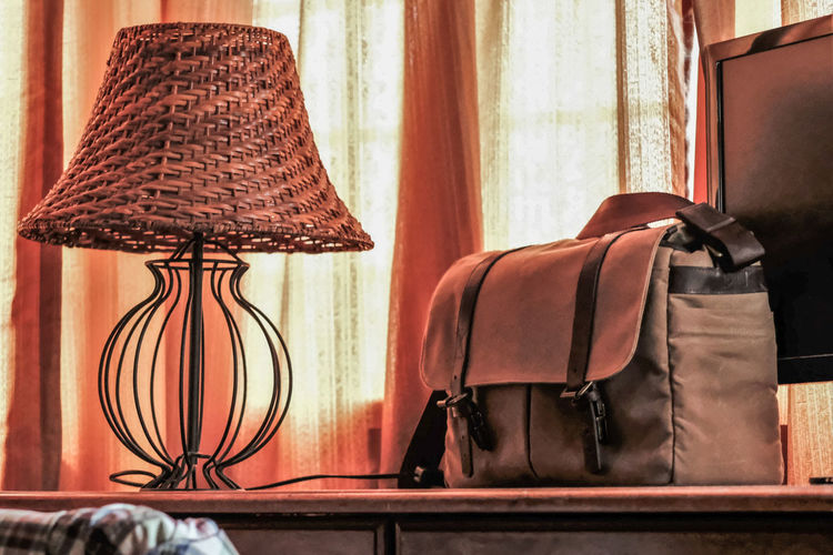 Close-up of bag and lamp on table