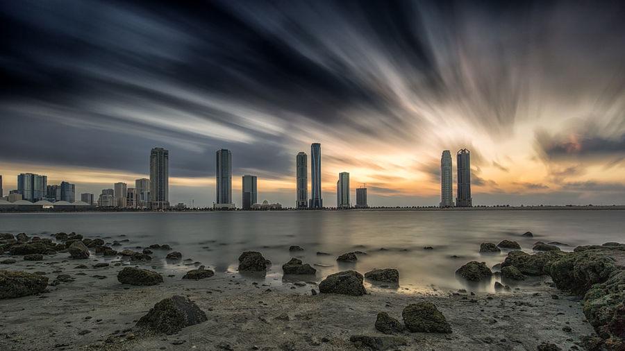 Sharjah Architecture Building Exterior Built Structure City Cityscape Cloud - Sky Long Exposure No People Outdoors Sea Sky Skyscraper Sunset Travel Destinations Urban Skyline Water
