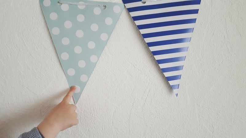 Flags Human Body Part Indoors  Pointing Finger Children Playing Decoration Showing Interior Design Party Celebration Birthday Shades Of Blue Baby Fingers Stripes Pattern Dots Home Interior Child Childhood Flags Garland High Angle View White Backgroud Minimalism Wall At Home