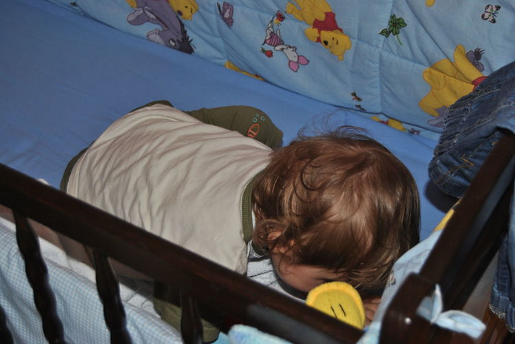 High angle view of baby boy in crib at home