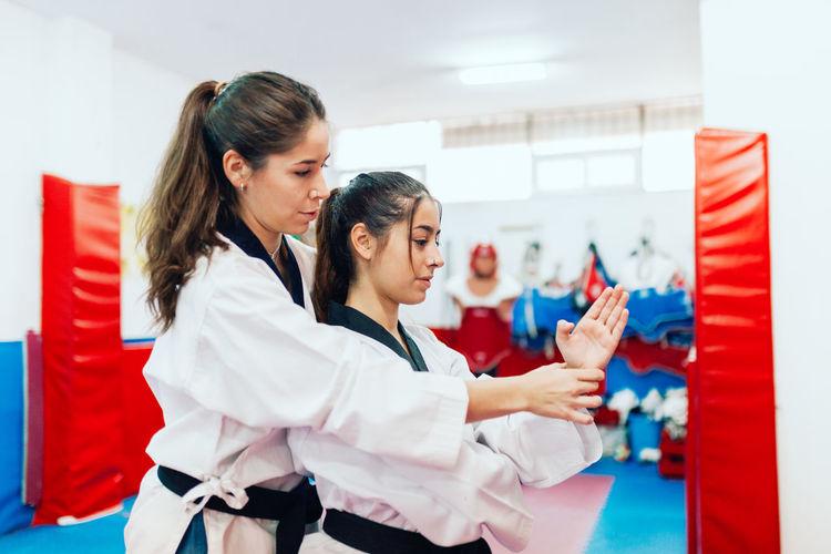 Taekwondo teacher guiding student during martial arts practice