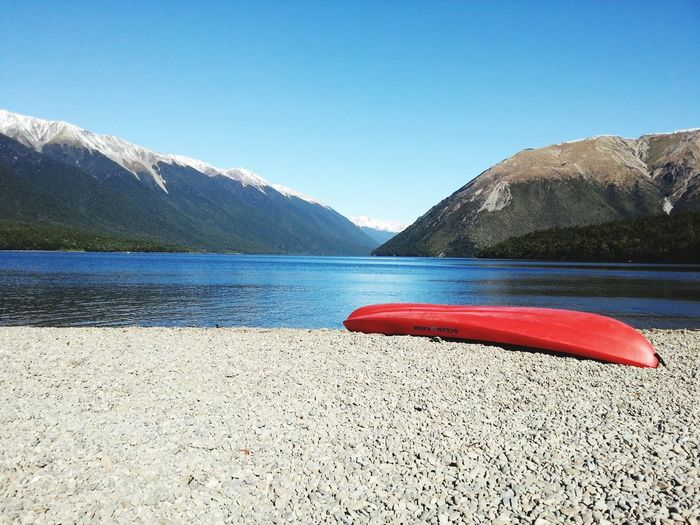 Canoeing in Nelson Lakes South Island Nelson Kiwi Kiwi Experience Nelson Lakes Nelson Lakes National Park Nelson Lake Park Canoe Canoeing New Zealand Beauty New Zealand Water Mountain Clear Sky Lake Beach Summer Nautical Vessel Sand Red Sunlight