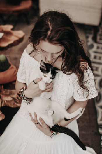 Young hippie woman in white boho blouse and skirt hugging the cat