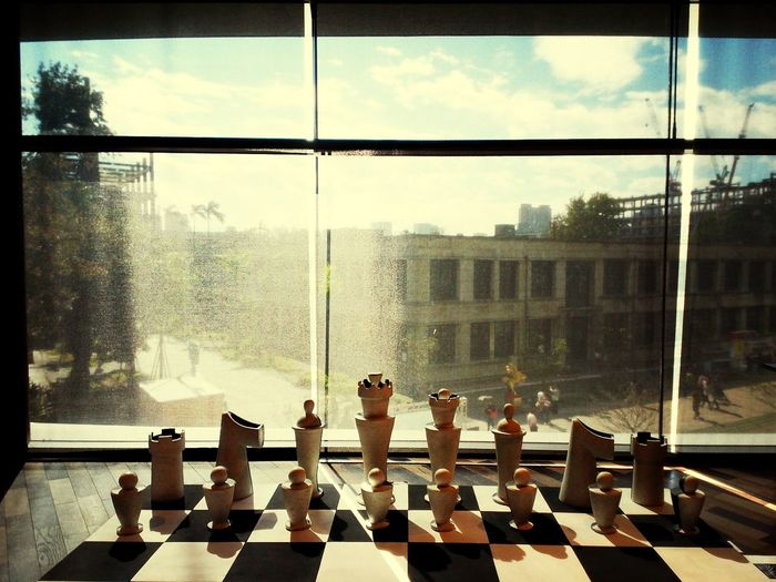 Chess pieces on chess board against window