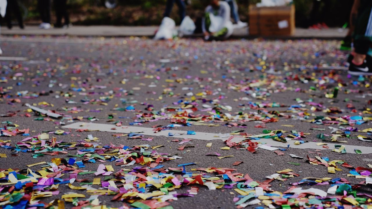 multi colored, large group of objects, confetti, abundance, focus on foreground, incidental people, day, celebration, close-up, high angle view, outdoors, event, still life, messy, jigsaw piece, falling, street, people, selective focus