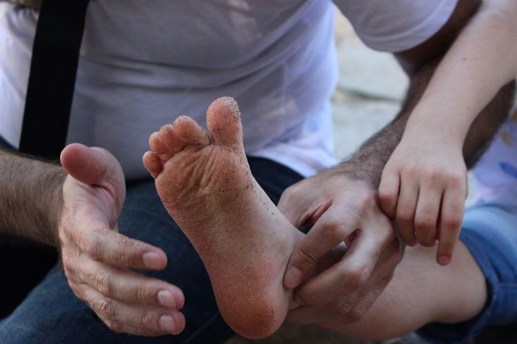 Midsection of man cleaning daughter dirty foot