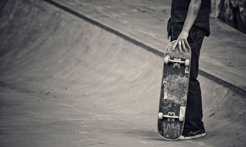 Low Section Of Man Standing With Skateboard On Sports Ramp
