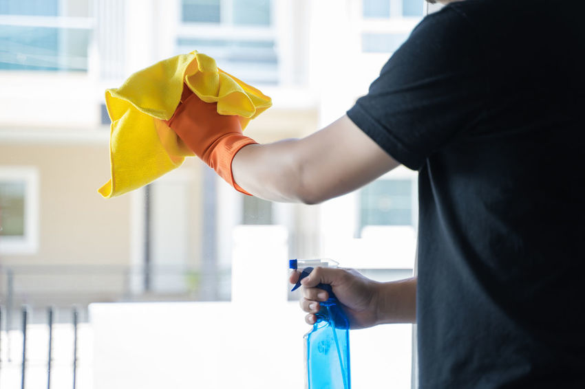 Holding One Person Real People Hand Human Hand Indoors  Lifestyles Midsection Focus On Foreground Casual Clothing Home Interior Standing Human Body Part Day Yellow Men Domestic Life Window Spray Bottle Spraying Housework