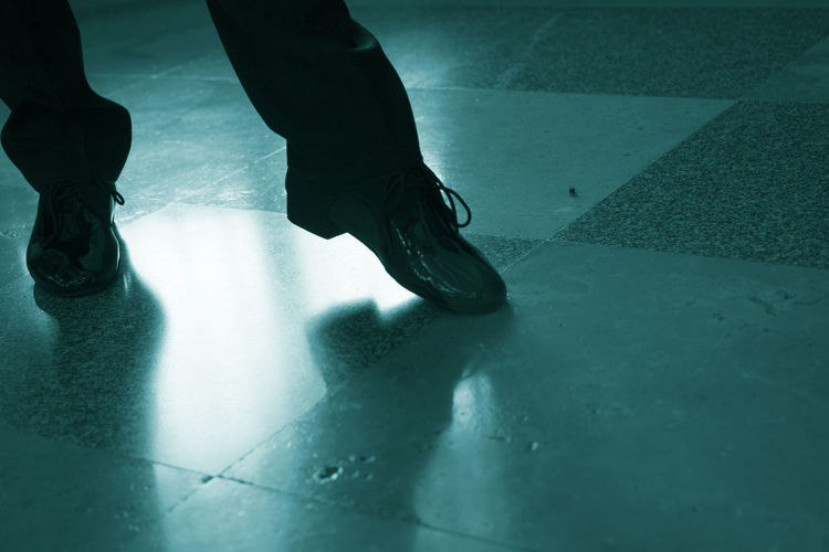 Low section of man dancing on tiled floor