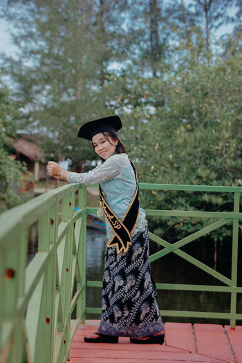 Portrait of smiling young woman standing on footbridge