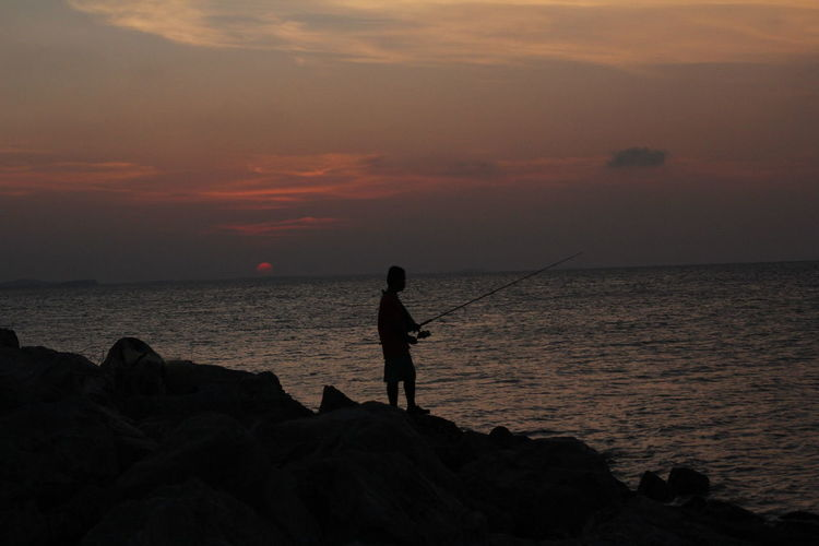 Silhouette man fishing on beach at sunset
