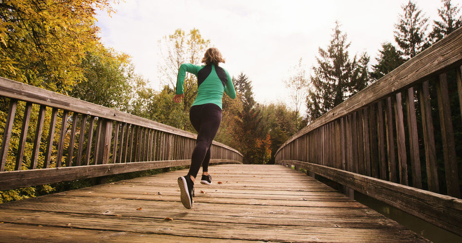 Activity Adult Athlete Bridge - Man Made Structure Day Exercising Footbridge Full Length Healthy Lifestyle Human Body Part Jogging Leisure Activity Lifestyles Motion Nature One Person Outdoors Real People Rear View Running Sport Sports Clothing Sports Training Vitality Wellbeing
