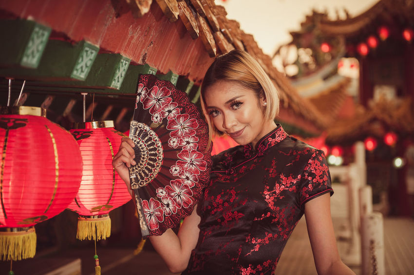 Beautiful Woman Celebration Focus On Foreground Front View Hanging Happiness Lantern Lifestyles Looking At Camera Night One Person Outdoors Paper Lantern People Portrait Real People Red Smiling Standing Tradition Young Adult Young Women