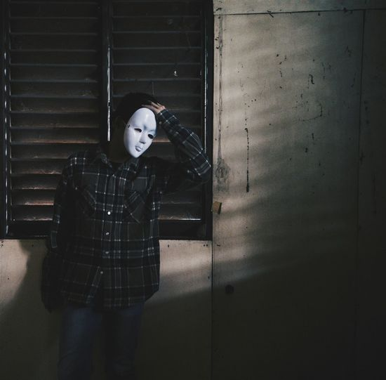 Man Wearing Mask Standing Against Window