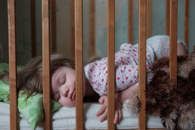 Close-up of girl sleeping in crib at home