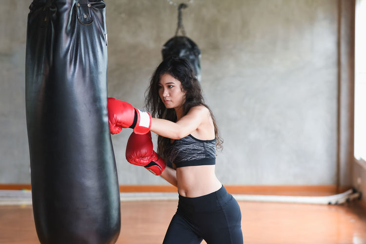 Young woman hitting punching bag in studio