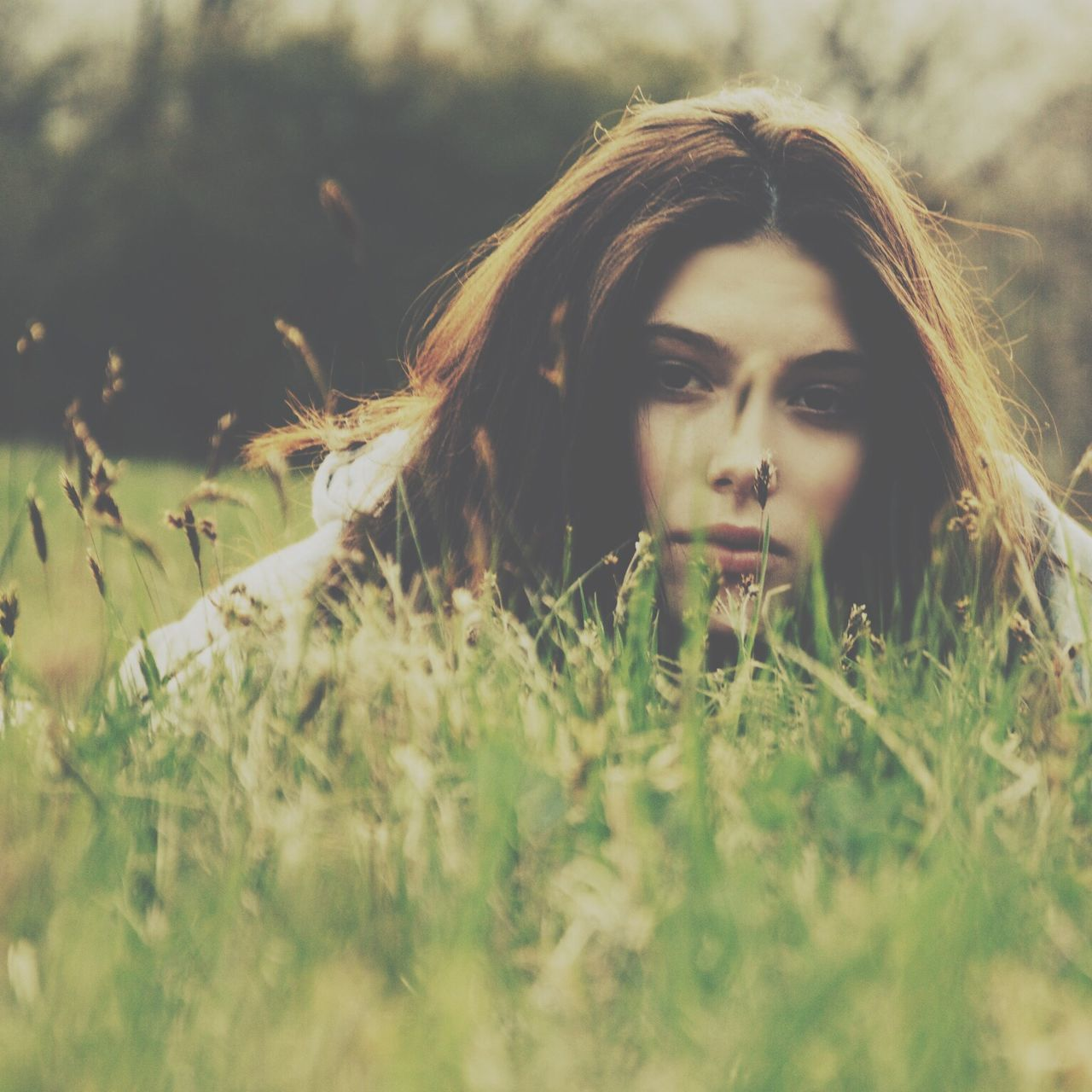 Portrait of beautiful young woman relaxing on grass in park