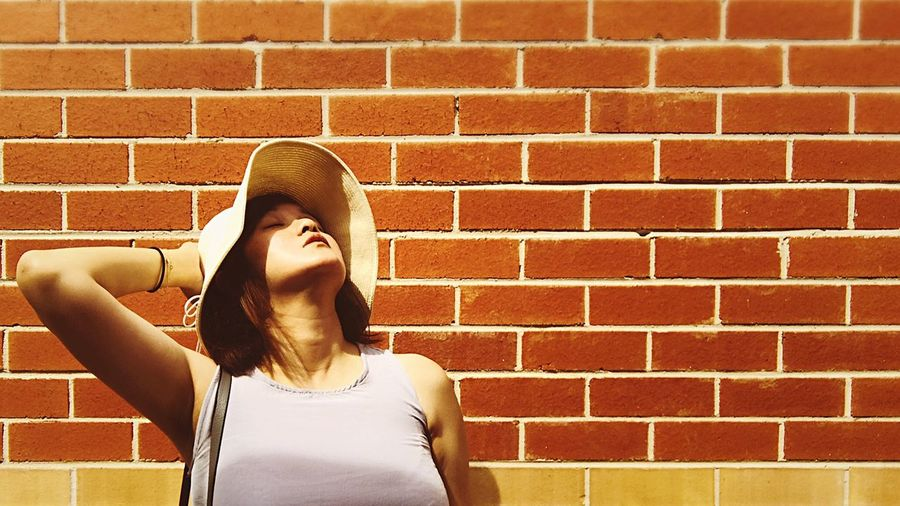 Woman Wearing Hat Standing With Head Back Against Brick Wall On Sunny Day