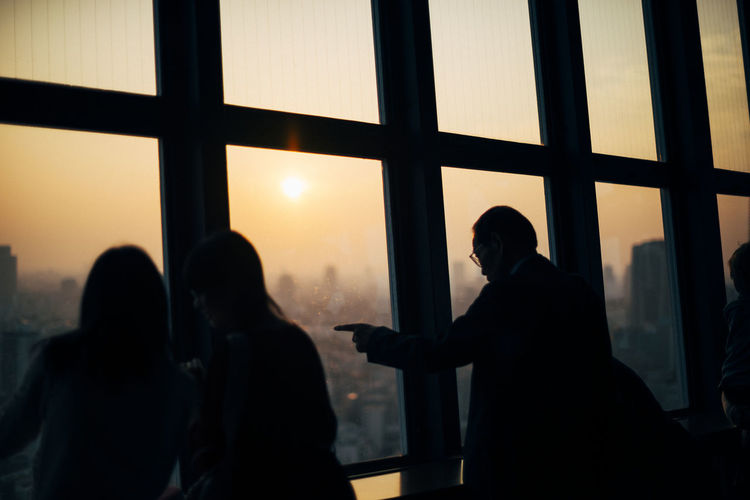 Silhouette people against window in city