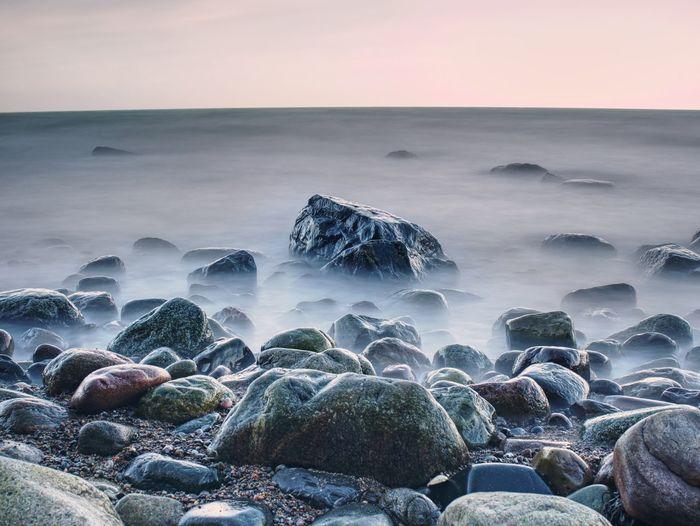 Beautiful seascape sea horizon and norwegian stone coastline, long exposure effect