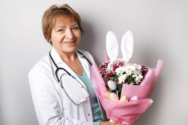 Portrait of smiling young woman holding flower bouquet
