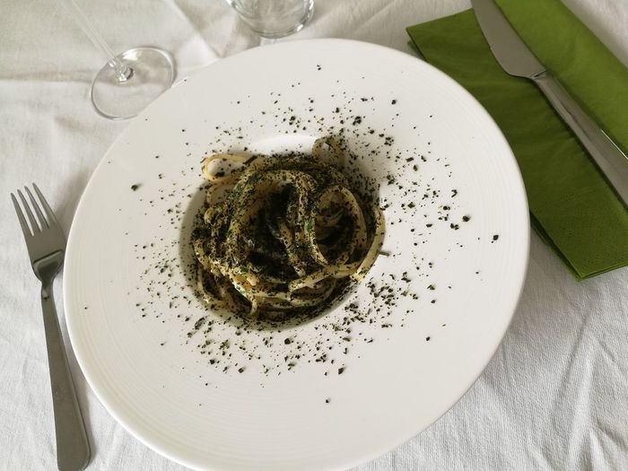 High angle view of garnished noodles in plate on table