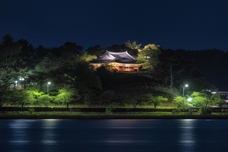 Illuminated building by lake against sky at night
