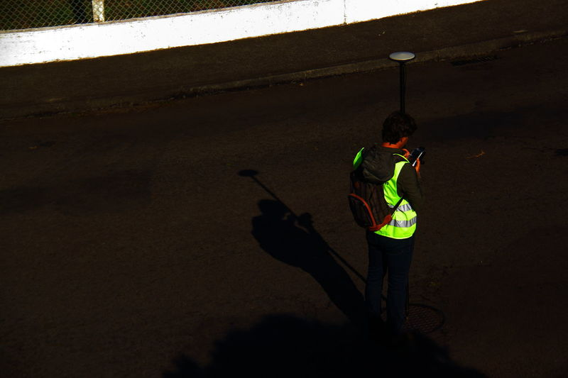Adult Adults Only Golfer In The Middle Of The Road Measurement Gauge Measurement Point Men One Man Only One Person Only Men Outdoors People Real People Rear View Road Rucksack Shadow Surveyor Technology Yellow Jacket Flying High