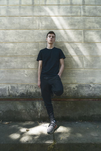 Full length of young man looking up against wall