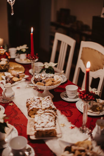 cookies and stollen on a festive table ready laid on Christmas eve Candle Burning Fire Food And Drink Celebration Table Flame Food Plate Indoors  Baked Sweet Food Sweet Event Dessert Cake Holiday Illuminated Freshness No People Glass Temptation Birthday Candles Setting Festive