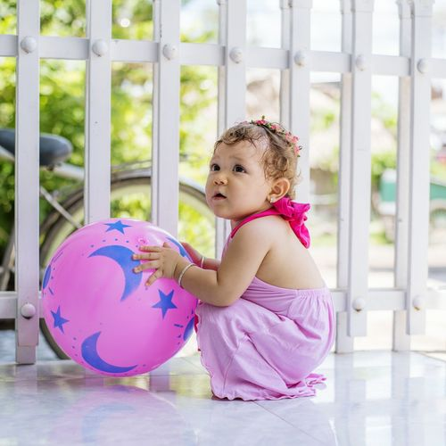 Cute Girl Playing With Ball At Porch