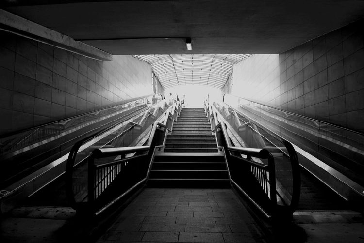 Low angle view of empty steps amidst escalators at subway station