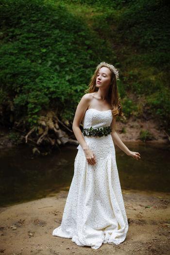 Beautiful woman in white dress standing at lakeshore