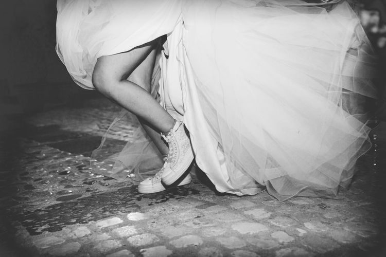 Low section of bride wearing shoes standing on cobbled street