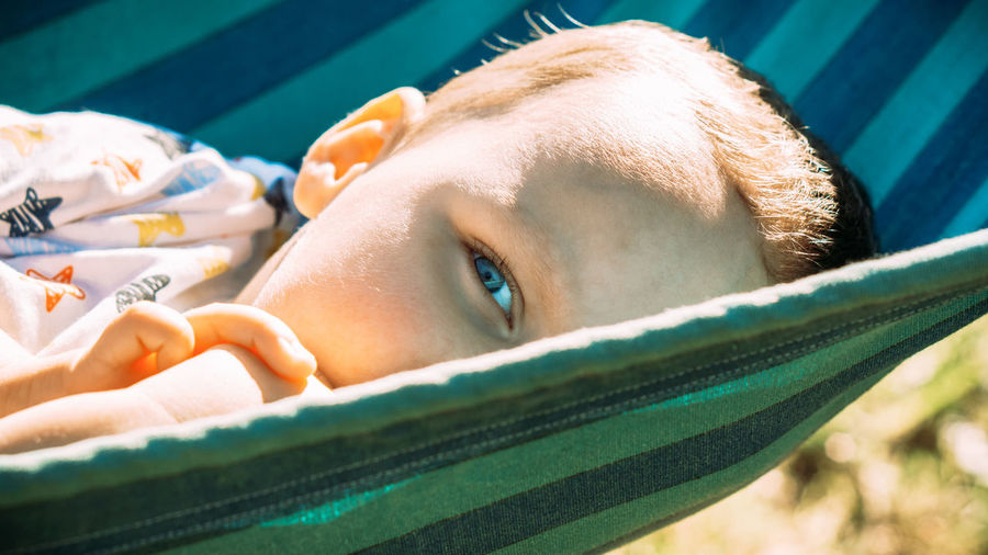 Close-up portrait of boy relaxing in swimming pool
