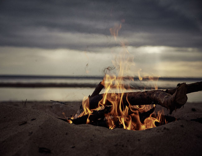 Low angle view of bonfire at dusk on beach