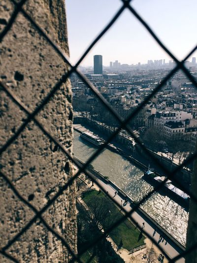 Seine River Amidst Cityscape Against Sky Seen Through Chainlink Fence