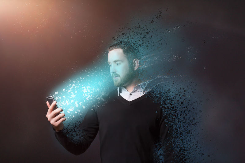 Digital composite image of dissolving man looking at illuminated mobile phone against abstract background