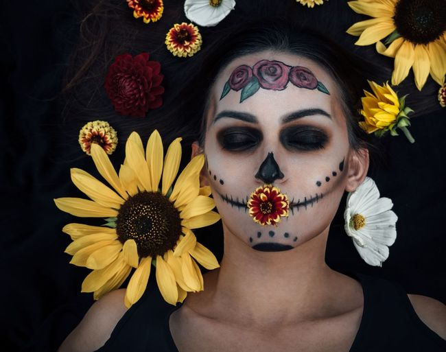 Woman with painted face amidst flowers