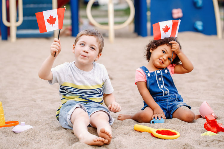 Portrait of boy and girl holding flags while playing with toys on sand