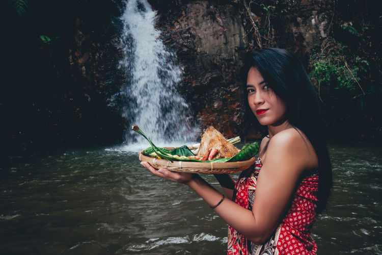 Portrait of woman holding food in tray against waterfall
