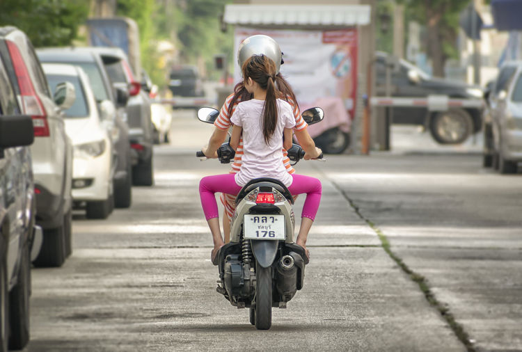 Rear view of woman riding motorcycle on street