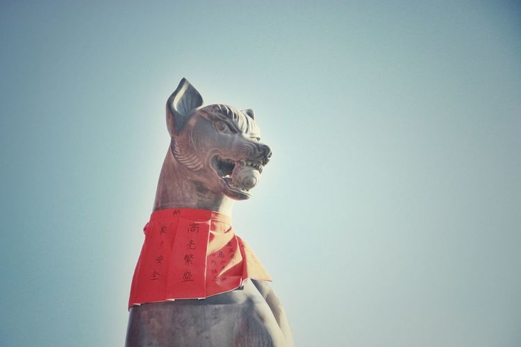 Low Angle View Of Fox Sculpture At Fushimi Inari Taisha Shrine Against Clear Sky