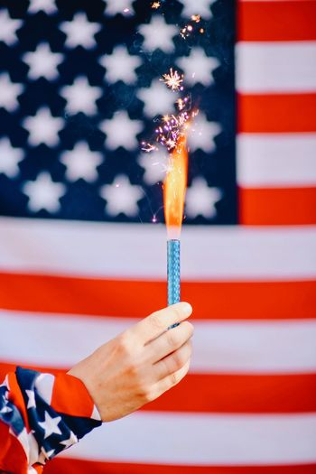 fireworks against the background of the American flag in honor of America's Independence Day Flag Patriotism Star Shape Human Body Part Human Hand One Person Shape Symbolism Adult Holding Symbol Government Blue Striped Pride Hand Democracy